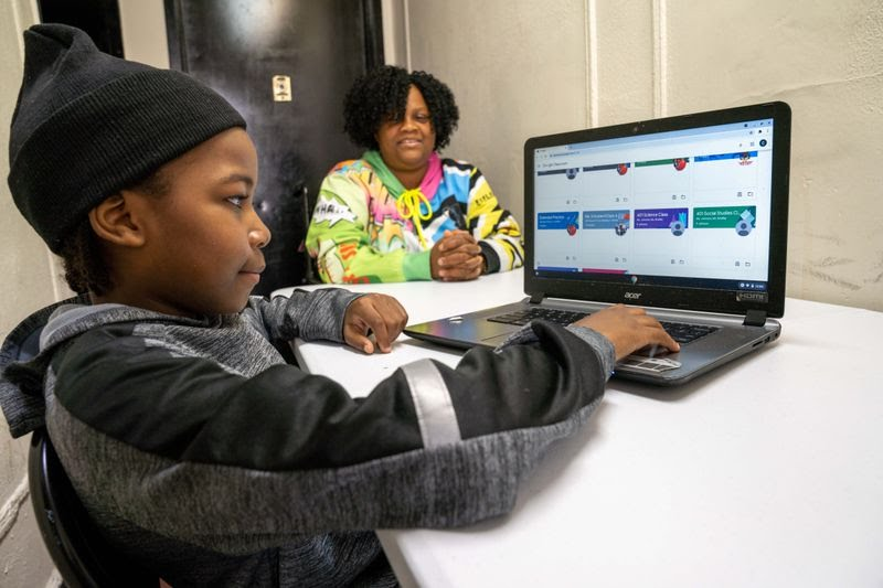Caleb is pictured on his laptop while his mother, Gwendolyn Livingstone, oversees his work Sunday in Brooklyn.